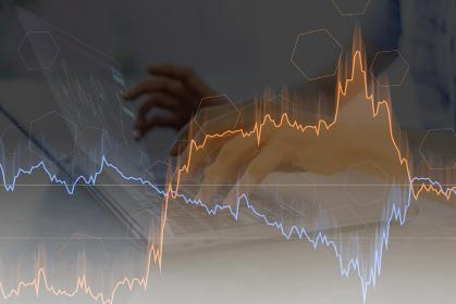 ノートPCを操作する女性の手と株価チャートの合成写真