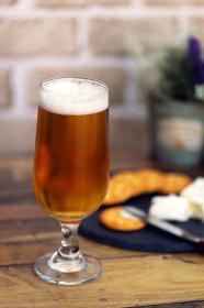 グラスに注がれたビールとカマンベールチーズとクラッカー