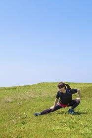 草原でストレッチをする女性