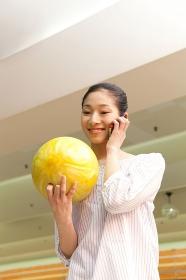 ボウリング球を持って電話する女性