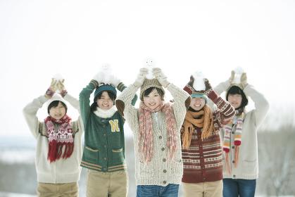 雪だるまを持ち微笑む中学生