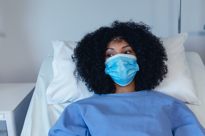African american female patient lying in hospital bed wearing face mask. medicine and health services during coronavirus covid 19 pandemic.