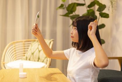 夜の部屋で美容ケアをする若い女性