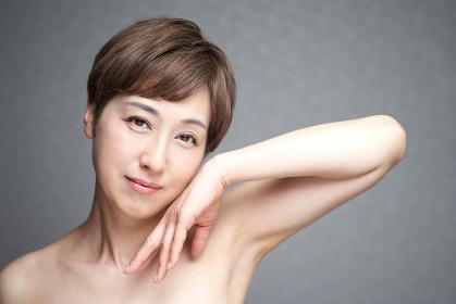 頬に手を当てる中年の日本人女性