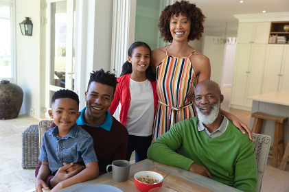 Portrait of smiling african american multi generation family sitting at table during breakfast. family enjoying quality free time together.