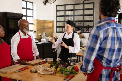 Side view of a multi-ethnic group of adults at a cookery class, the diverse adult students listening to instructions from a Caucasian female chef wearing chefs whites and a black hat and apron, standing around a wooden table of ingredients