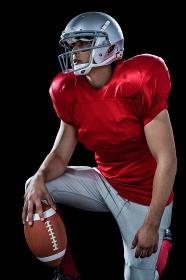 Sportsman holding American football while kneeling