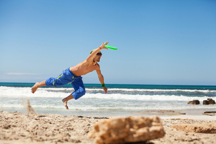young sporty man in the jump in beach volleyball