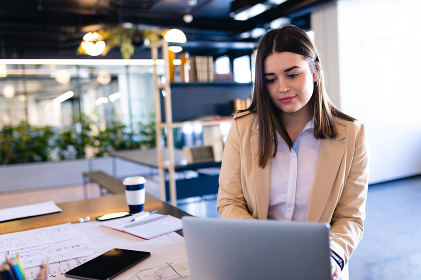 Front view of a Caucasian businesswoman wearing smart clothes, working in a modern office, sitting by a desk and using her laptop. Social distancing and self isolation in quarantine lockdown