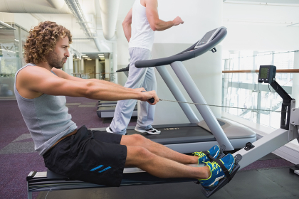 Fit young man on fitness machine at gym
