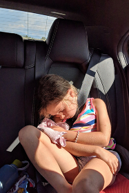 Little girl asleep in her car seat with her favorite stuffed toy