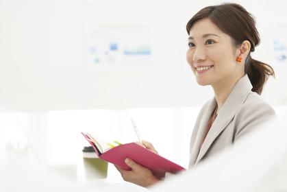 手帳を持っている笑顔のビジネスウーマン