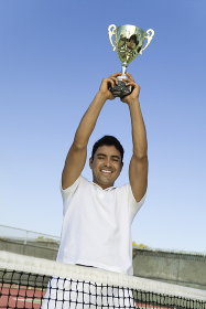 Tennis Player on court by net Holding Trophy Over Head portrait