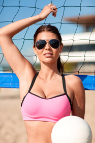 young woman with volleyball ball and net on beach