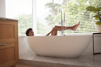 Mixed race woman spending time at home self isolating and social distancing in quarantine lockdown during coronavirus covid 19 epidemic, taking a foamy, warm bath and relaxing.