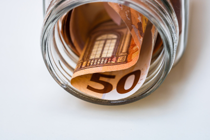 Composition with saving money banknotes (50 EURO) in a glass jar. Concept of investing and keeping money, close up isolated.
