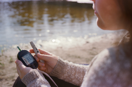 Diabetic woman making analysis for sugar while sitting near the river.