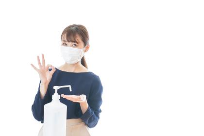 マスクを装着してOKサインをする若い女性