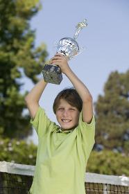 Boy on tennis court Holding up Tennis Trophy portrait