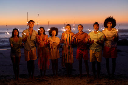 A multi-ethnic group of friends enjoying their time together on a beach during sunset, standing in a row, holding sparklers, looking at the camera and smiling