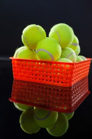 Close up of tennis balls in red plastic basket with reflection