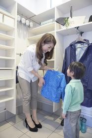 男の子にレインコートを着せる母親