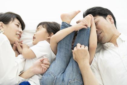 寄り添って横になる家族4人