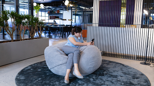 Front view of an Asian businesswoman wearing smart clothes, working in a modern office, sitting on a bean bag and using her smartphone.