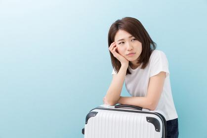 女性とスーツケース 考える