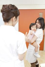 手を振る看護師と母子