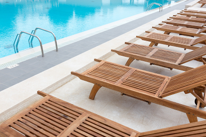 Luxury swimming pool with wooden deck chairs.