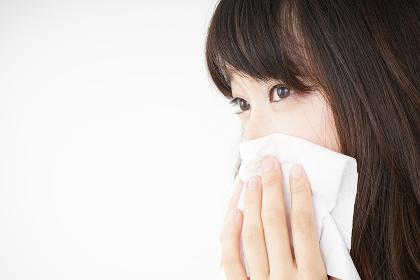鼻をかむ若い女性