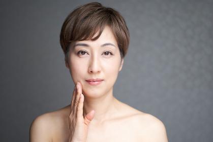 口角を押さえてカメラ目線で微笑む中年の日本人女性
