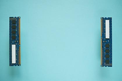 青い紙の上に部品面を見せて間を空けて左右に置いた二枚のデスクトップパソコンのDDR3増設メモリー