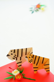 年賀状に使える白い背景に飾りと折り紙の2頭の黄色い虎とホワイトタイガー縦構図