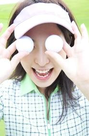 ゴルフボールを目に当てる女性