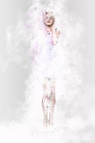 白いワンピースを着たショートヘアのクールな女性がサングラスをかけながら白い煙のなかに佇んでいる