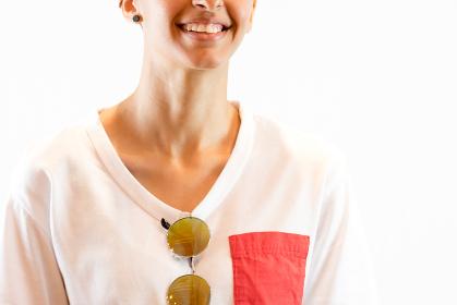 首元にサングラスをかけた笑顔の女性