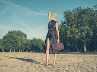 Vintage filtered shot of an elegant young woman wearing a dress and a hat standing in the park with a briefcase