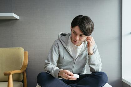 自宅の部屋でワイヤレスイヤホンを耳につける若い男性