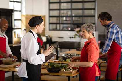 Side view of a multi-ethnic group of Senior adults at a cookery class, the diverse adult students listening to instructions from a Caucasian female chef wearing chefs whites and a black hat and apron, standing at wooden tables of ingredients preparing food