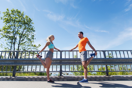 smiling couple stretching outdoors
