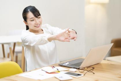 カジュアルな空間での仕事中のストレッチする女性