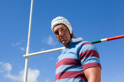 Portrait of rugby player wearing white helmet against blue sky