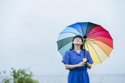 雨の中、カラフルな傘を指す女性