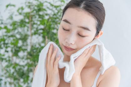 タオルで顔をふく若い女性