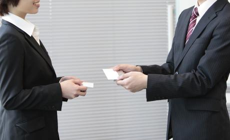 名刺交換するビジネスマンとビジネスウーマン