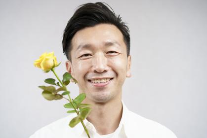 黄色い薔薇の花を持つ男性・父の日イメージ