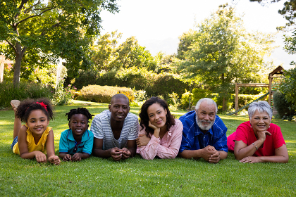 Front view of a multi-ethnic, multi-generation family outside in the garden, lying on the grass together in a row, facing the camera and smiling