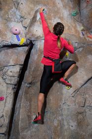 Rear view of woman practicing rock climbing